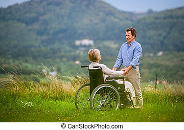 Senior man with woman in wheelchair, green autumn nature