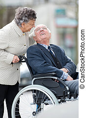 senior man with woman in wheelchair outside in the city