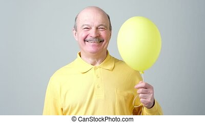 Senior man with yellow balloon with helium in hand - Happy...