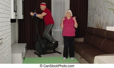 Senior man, woman doing vitality weight lifting sport dumbbells exercises and using orbitrek in living room. Old people pensioner grandfather and grandmother healthy training healthcare sport at home