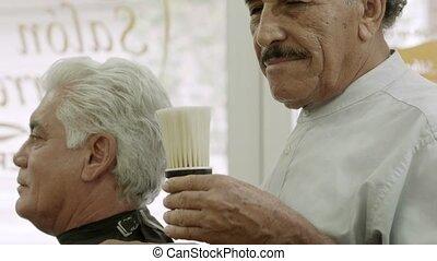 Senior man working as barber