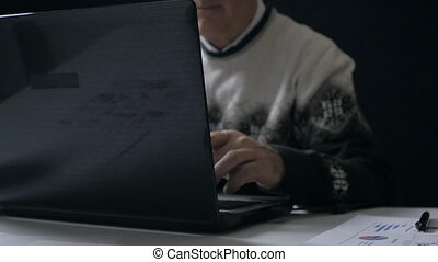 Senior man working at a laptop in dark room