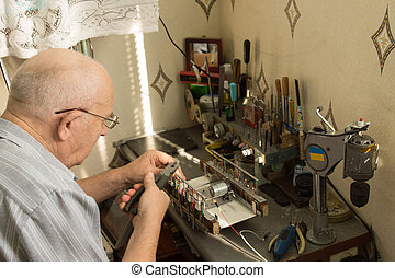 Senior man working at a small work bench