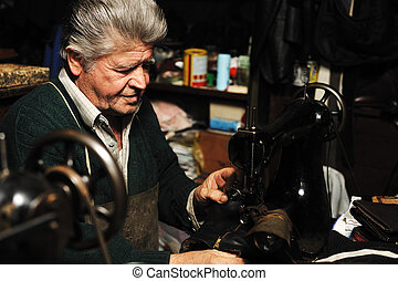Senior man working with old machine in his own workshop