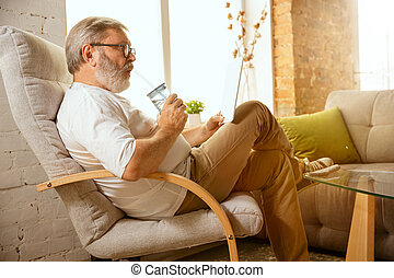 Senior man working with tablet at home - concept of home studying