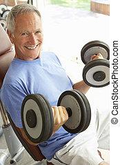 Senior Man Working With Weights In Gym