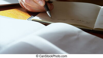 Senior man writing on diary in kitchen at home 4k - Close-up...