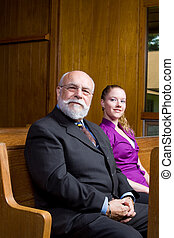 Older Caucasian man and young woman sitting in church pew, smiling at camera.