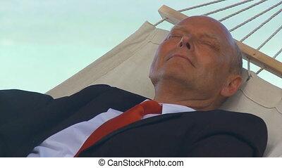 senior manager sleeping in hammock close