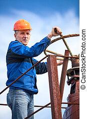 Senior manual worker turning huge valve gate at factory