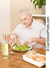 Senior mature man eat vegetable salad and white wine at...