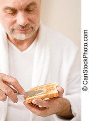 Senior mature man having breakfast toast - Senior mature man...