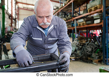 senior mechanic working in a factory