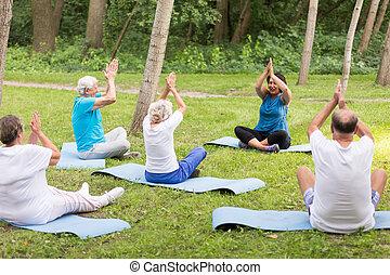 Senior men and women doing yoga