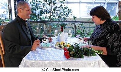 Senior Men And Women Eating Dessert At The Cafe.