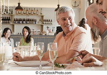 Senior Men Socialising At A Dinner Party - Senior men are...