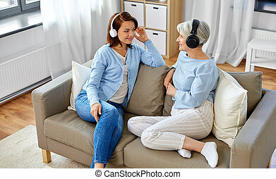 senior mother and adult daughter with headphones