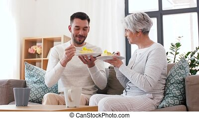 senior mother and adult son eating cake at home - family,...