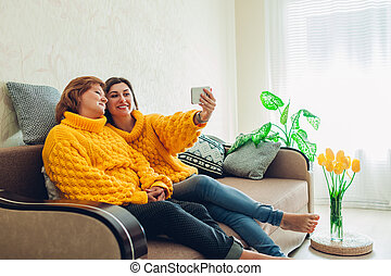 Senior mother and her adult daughter taking selfie using smartphone at home. Mother's day concept.