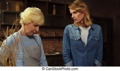 Senior mother and her daughter daughter having a misunderstanding in the kitchen