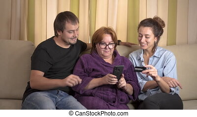 Senior mother and her young daughter and son using tablet at home. Shopping with credit card on cellphone. Teen granddaughter teaching grandmother how to use mobile and make purchases online