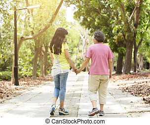 senior mother with daughter walking in the park
