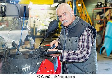 senior motorcycle mechanic is fixing a classic motorbik