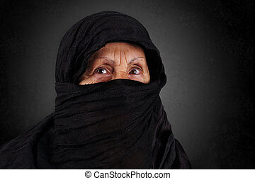 Senior muslim woman with black hijab - Dramatic portrait of...