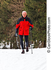 Senior Nordic Walking in winter - Senior at the snow in...
