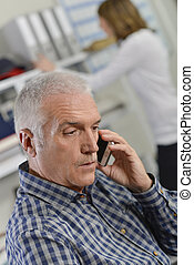 Senior office worker on the phone