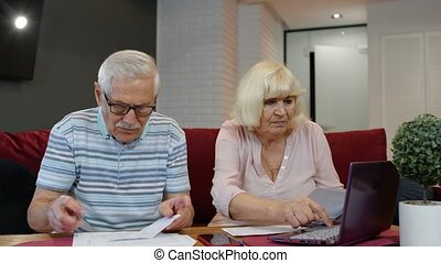 Worried senior old couple stressed about paperwork discuss unpaid bank debt holding bills check expenses, retired aged family read loan payments documents talking at home anxious about money problems
