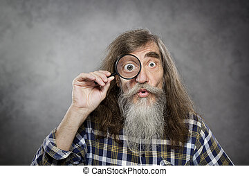 Senior old man looking through zoom magnifying glass. Funny...