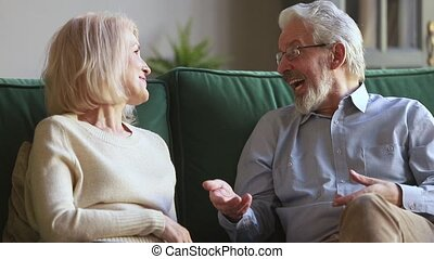Senior old spouses couple talking sitting on sofa at home -...