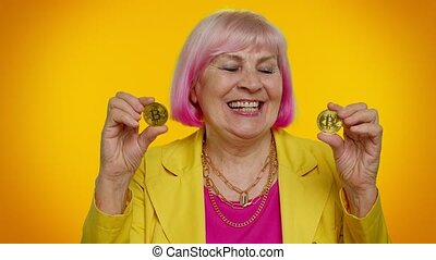Cheerful senior old stylish granny woman in jacket showing golden bitcoins. Achievement career wealth, cryptocurrency investment, mining, future technology. Elderly grandmother on yellow background