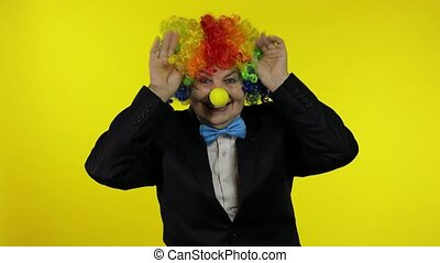 Senior old woman clown in colorful wig smiling, making silly faces, fool around