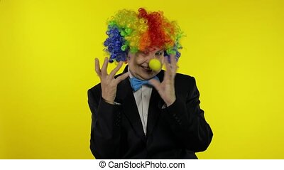 Senior old woman clown in wig having fun, smiling, dancing, making silly faces