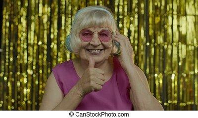 Senior old woman dances, listens music on headphones. Having fun, smiling, showning thumb up