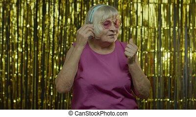 Senior old woman dances, listens music on headphones. Relaxing, enjoying, having fun, smiling