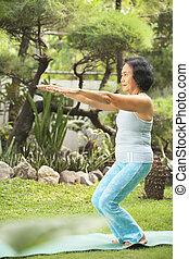 Senior old woman doing yoga in park