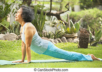 Senior old woman doing yoga in park