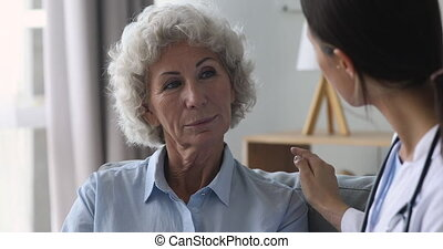 Senior old woman patient talking to doctor at checkup consultation