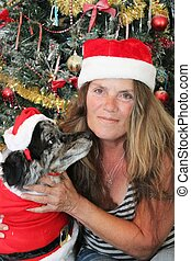 Senior oman with her dog in Christmas outfit