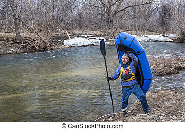 senior paddler carrying a packraft