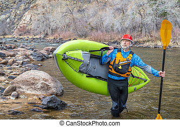 senior paddler carrying inflatable whitewater kayak - senior...