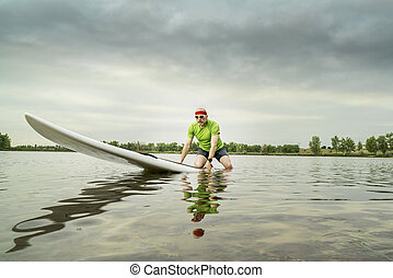 senior male paddler on a paddleboard, lake in northern Colorado, clody summer morning