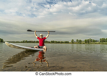 senior male paddler sitting on a paddleboard, lake in northern Colorado with an early summer scenery