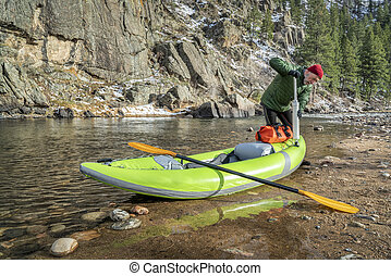 paddler pumping up inflatable whitewater kayak - senior...