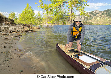 Senior paddler with expedition stand up paddleboard