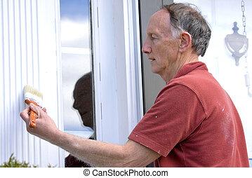 Senior painter - Senior man painting outside of house