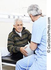 senior, patiënt, kijken naar, fysiotherapeut, op bed
